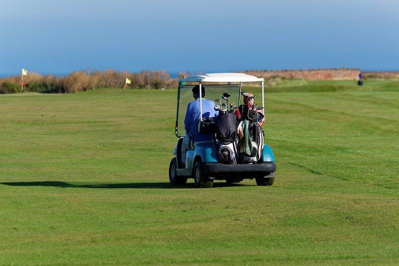 Golfspelare i golfbil reser med Golfhäftet
