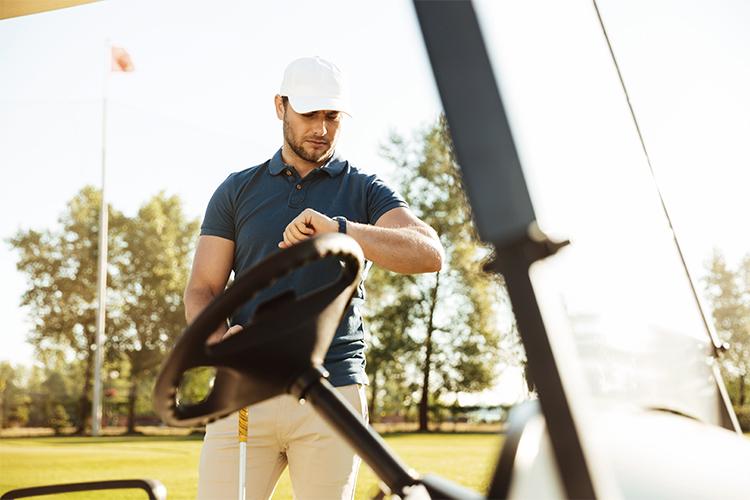 Golfklockor - golfare står vi golfbil och kollar på en klocka
